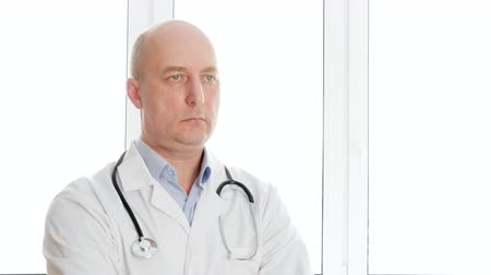 healthy office : Portrait doctor in white lab coat with phonendoscope nodding head YES and NO in clinic office. Practitioner with stethoscope positively shaking head in medical hospital in window background Stock Footage