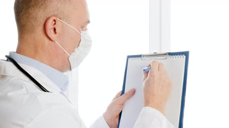 liste : Male doctor in white coat and protective mask writing coronavirus on clip board in hospital. Virologist in medical gown and mask writing coronavirus diagnosis in clinic office.