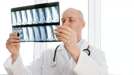 csontok : Doctor looking at X-ray of backbones and nodding head YES. Serious middle aged male doctor in white coat with stethoscope examining X-ray image in hospital Stock mozgókép