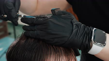 cavalheiro : Cropped shot of barber cutting hair to male client. Close-up partial view of hairdresser holding comb with scissors and grooming man in barber shop Stock Footage