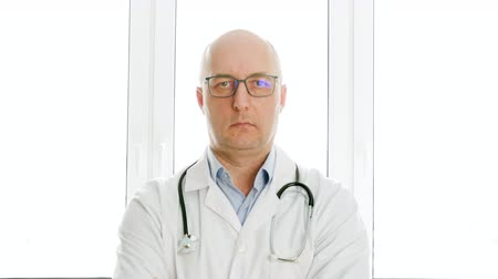 sallama : Serious middle aged doctor nodding head and shaking head NO and YES sign. Portrait of confident male doctor in white coat with stethoscope shaking head and looking at camera in hospital Stok Video