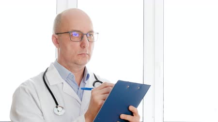 liste : Serious middle aged doctor holding clipboard and writing diagnosis in clinic. Professional male doctor in white coat with stethoscope thinking and writing checklist in hospital