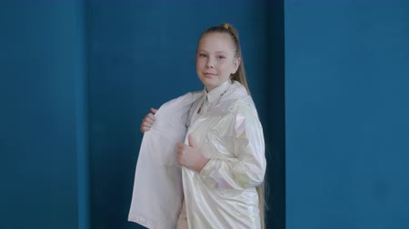 long hair : Beautiful teenage girl in fashionable glossy jacket looking at camera. Portrait of adorable trendy teen girl with long hair wearing stylish white coat and posing on blue background