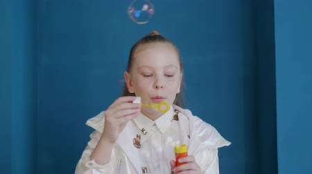 camsı : Cute girl blowing soap bubbles and looking at camera. Close-up portrait of adorable teenage girl blowing soap bubble on blue background