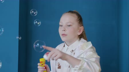 camsı : Adorable teenage girl playing and blowing soap bubbles. Adorable girl having fun with soap bubbles and looking aside on blue background
