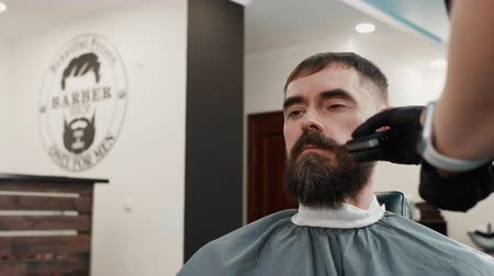 navalha : Bearded man getting shaving beard with electric razor in barbershop. Barber shaving beard with trimmer in male beauty salon. Male beard care concept