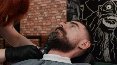 grzebień : Barber shaving beard with electric trimmer and comb in barbershop. Process trimming beard with electric razor in male salon. Handsome man shaving beard in barber salon Wideo