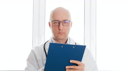 liste : Doctor in white coat writing on clip board while medical checkup in hospital. Practitioner with stethoscope writing medical examination in check list in clinic office