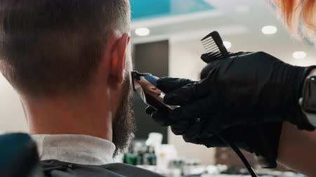 beard trim : Close up shaving beard with electric clipper in barber salon. Barber trimming beard with electric razor in male salon. Professional shaving hipster beard