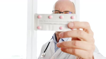 ajánlás : Doctor holding tablet blister front camera close up. Male pharmacist showing drug pills to camera in pharmacy office Stock mozgókép