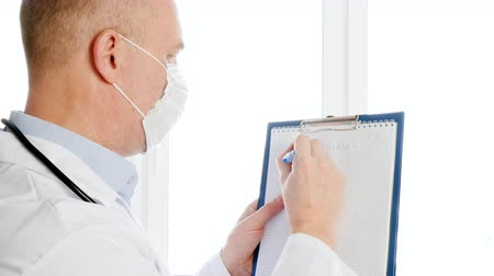 bio hazardous : Scientist holding clipboard with coronavirus question. Doctor wearing facial mask writing coronavirus inscription on paper. Coronavirus infection concept