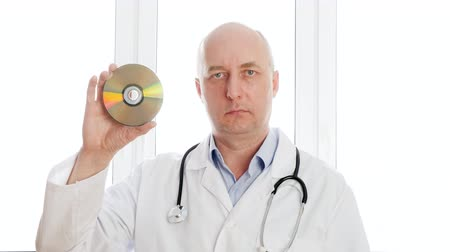 compact disc : Bald doctor showing CD disk front camera on white window background. Medical worker holding in hands DVD data disk and looking to camera in clinic technical laboratory