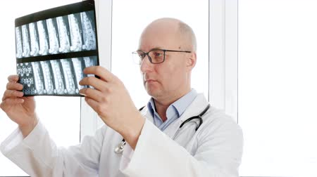 csontok : Man surgeon looking backbones x-ray front window in clinic office. Male doctor holding x-ray spine bones looking to camera. Portrait doctor in medical gown with phonendoscope Stock mozgókép