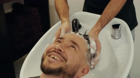 szampon : Hairdresser hand washing head of happy man in male salon. Hair stylist washing male head with shampoo in barbershop. Bearded man getting wash hair in barber salon Wideo