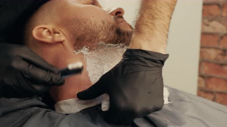 shaving foam : Close up barber hands shaving bearded man with straight razor in male salon. Process shaving beard with razor and foam in barber shop. Male beard care concept Stock Footage