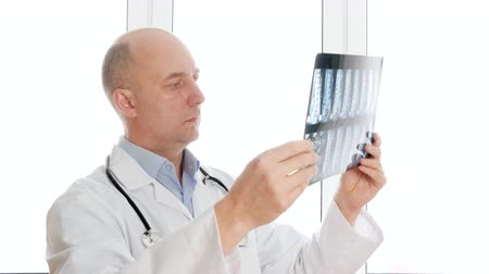 スキャン : Male radiologist in white overall holding x-ray. Professional medical worker doctor surgeon inspecting x-ray while standing near window. Medicine concept