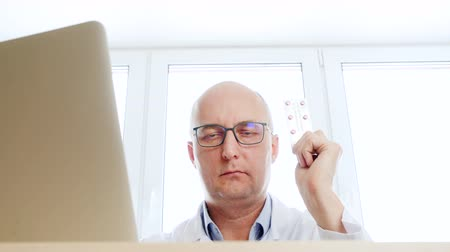 macacão : Low angle view of doctor recommending drug pills. Confident male pharmacist holding pills tablet and nodding head while sitting at table with laptop. Medical consultation concept