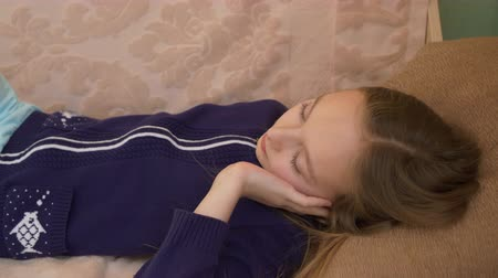 растягивание : Thoughtful little girl lying on sofa. Lovely young girl holding hand on chin, stretching and napping. Sleeping concept