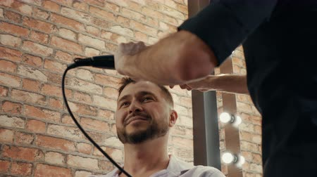 hairstyliste : Handsome man drying hair in barber shop. Barber using hair dryer and comb for male hairstyle. Hairstylist drying hair with brush in male salon Stockvideo