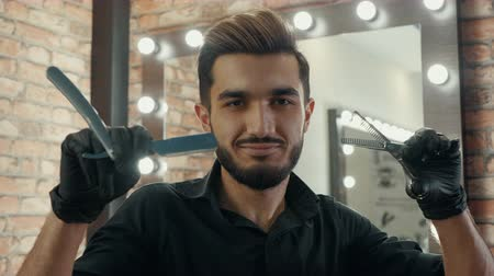 cortador : Smiling hairdresser snapping scissors front camera in fashion barbershop. Portrait winking barber with straight razor and scissors posing to camera in hair salon