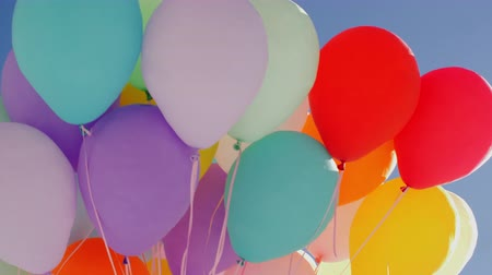 díszítés : Many colorful balloons flying in blue sky background. Bunch colorful air balls flying in transparent blue sky