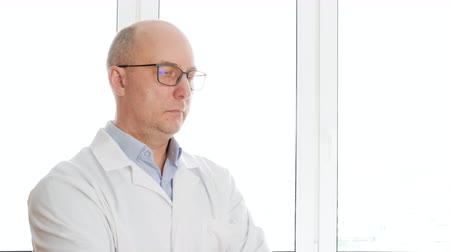 harmincas : Portrait scientist bald man in glasses and white coat looking away on white window background. Bio engineer in white coat standing front window in office