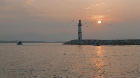 sombrio : Boats passing lighthouse with rising sun at background. Vídeos