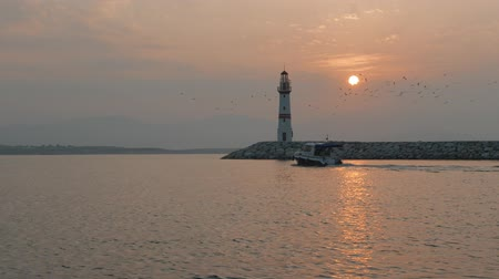 sombrio : Boats passing lighthouse with rising sun at background. 4K. Vídeos