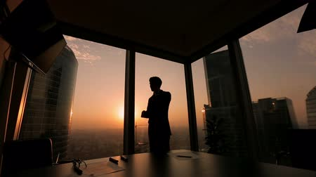 investimento : businessman standing at the window at sunset and talking on the phone gesticulating, Dolly shot