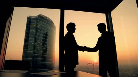 discussão : silhouette of two businessmen talking and shaking hands standing by the window at sunset, the construction of a skyscraper and crane in the background
