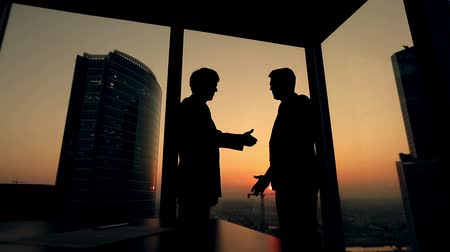 рукопожатие : silhouette of two businessmen talking and shaking hands standing by the window at sunset, the construction of a skyscraper and crane in the background