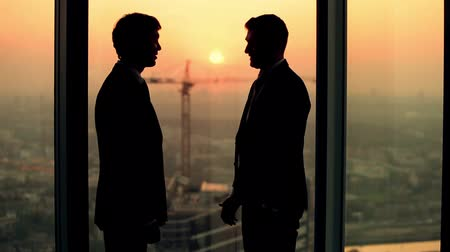 siluety : silhouette of two businessmen talking and shaking hands standing by the window at sunset, the construction of a skyscraper and crane in the background