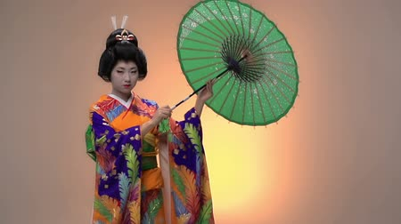 головной убор : Japanese Geisha performer posing with sun parasol in studio, slow motion Стоковые видеозаписи