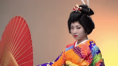 Японская культура : Japanese geisha performer posing in Studio with umbrellas, slow motion