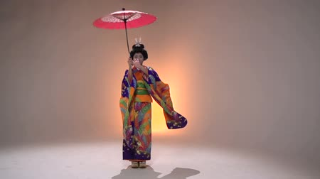 головной убор : Japanese geisha performer posing in Studio with umbrellas, slow motion