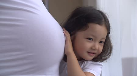 acariciando : Curious little girl listening to her pregnant mothers belly,dolly shot, slow motion Vídeos