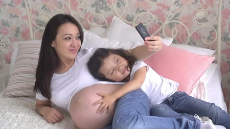 young pregnant Asian woman with her little daughter having fun taking selfies on the bed Stock mozgókép