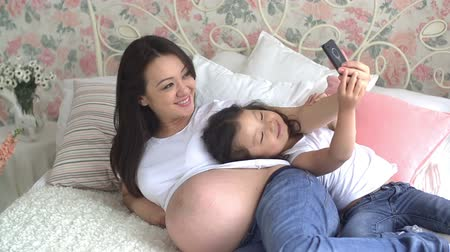 to take : young pregnant Asian woman with her little daughter having fun taking selfies on the bed Stock Footage