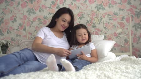 young pregnant Asian woman with her little daughter have fun playing with tablet on the bed