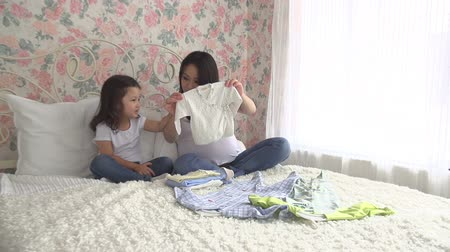 pregnant long term Asian mother and daughter prepare clothes for the new baby Stock mozgókép