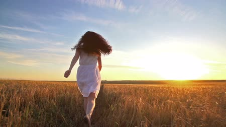 a young girl happily running through a field of Golden wheat at sunset, slow motion, rear view
