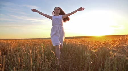 a young girl smiles happily and runs across the field of Golden wheat at sunset, slow motion