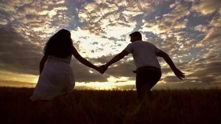 young happy couple is taken by the hand and runs to hug and kiss in the open field of Golden wheat, the silhouette with dramatic clouds