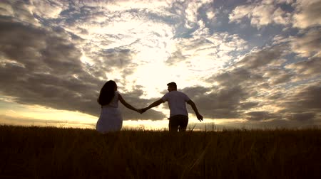 young happy couple is taken by the hand and runs into the open field of Golden wheat, the silhouette with dramatic clouds