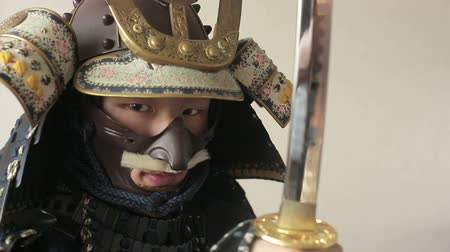 korkunç : ancient Japanese samurai with katana menacingly posing, close up, white background Stok Video