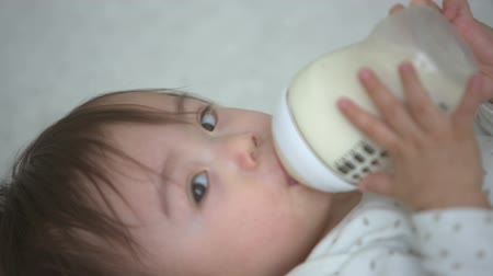 bottle feeding : asian baby drinking from bottle,close up