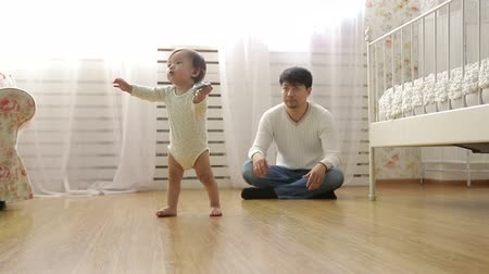 stepping : father teaches baby to walk,dolly shot