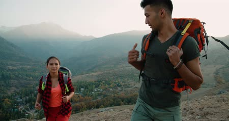 podróżnik : a couple of Asian hikers in the mountains, the boyfriend helps the girl holding her hand