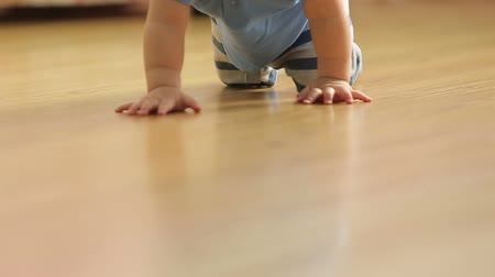 ilerici : a little funny baby crawling on the floor, back view,slowmotion