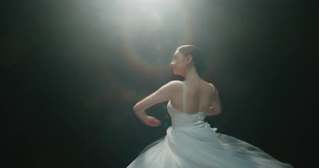 bale : 4K video footage closeup of a beautiful female ballet dancer on black background, slow motion